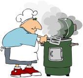 Uomo che cucina su un fumatore Fotografia Stock Libera da Diritti