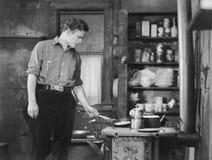 Uomo che cucina sul woodstove immagine stock libera da diritti