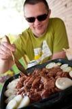 Uomo che cuoce carne e le cipolle alla griglia Fotografie Stock
