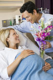 Uomo che dà alla sua moglie incinta i fiori fotografia stock