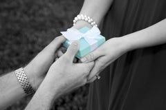 Uomo che dà a donna un contenitore di regalo fotografie stock libere da diritti