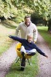 Uomo che dà giro del figlio in carriola immagini stock libere da diritti