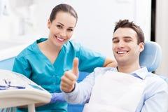 Uomo che dà i pollici su all'ufficio del dentista Immagini Stock