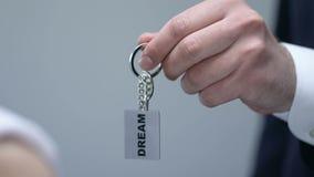 Uomo che dà il keychain della donna con la parola di sogno, concetto di motivazione, direzione stock footage