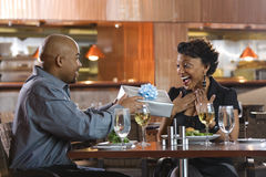 Uomo che dà regalo alla donna al ristorante Fotografia Stock Libera da Diritti