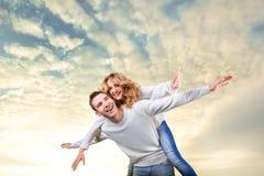 Uomo che dà sulle spalle giro all'amica sotto il cielo Fotografia Stock