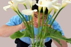 Uomo che dà una occhiata attraverso i fiori Fotografia Stock Libera da Diritti