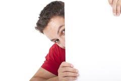 Uomo che dà una occhiata dietro il tabellone per le affissioni bianco vuoto Fotografia Stock