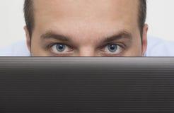 Uomo che dà una occhiata sopra il computer portatile Immagine Stock