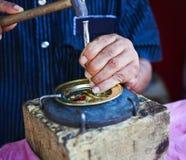 Uomo che decora piatto dorato con il fuoco stretto Fotografie Stock