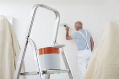 Uomo che decora stanza con la latta di pittura e della spazzola in priorità alta Fotografia Stock Libera da Diritti