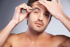 Uomo che depila le sue sopracciglia. immagini stock