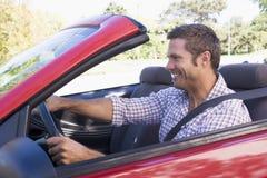 Uomo che determina sorridere convertibile dell'automobile Fotografie Stock