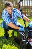 Uomo che di svuotamento il collettore dell'erba della falciatrice Fotografia Stock Libera da Diritti