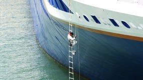 Uomo che dipinge l'arco di una nave Immagine Stock Libera da Diritti