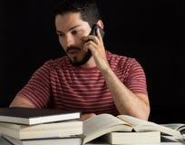 Uomo che discute a fondo il telefono con i libri Fotografia Stock Libera da Diritti