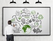 Uomo che disegna gli schizzi rinnovabili di fonti di energia alla lavagna Fotografia Stock Libera da Diritti