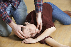 Uomo che dispone donna nella posizione di recupero dopo l'incidente Fotografie Stock Libere da Diritti