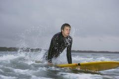Uomo che distoglie lo sguardo mentre praticando il surfing in acqua alla spiaggia fotografia stock