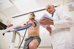 Uomo che effettua la prova di forma fisica sulla bici di esercizio Immagini Stock