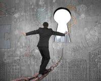 Uomo che equilibra sulla vecchia catena del ferro verso il buco della serratura con paesaggio urbano Fotografia Stock