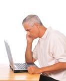 Uomo che esamina attento il computer portatile Fotografia Stock
