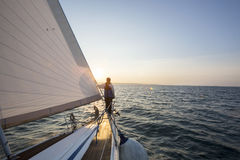 Uomo che esamina bello mare dalla prua della barca a vela immagine stock