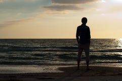 Uomo che esamina fuori la spiaggia Immagine Stock