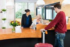 Uomo che esamina i receptionist in hotel Immagini Stock Libere da Diritti