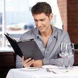 Uomo che esamina il menu delle bevande Immagini Stock