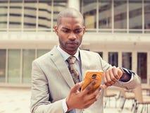 Uomo che esamina l'orologio del telefono cellulare che esaurisce tempo Immagini Stock
