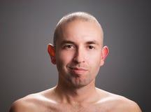 Uomo che esamina macchina fotografica con un mezzo sorriso Immagini Stock