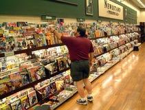 Uomo che esamina rivista in una libreria immagine stock