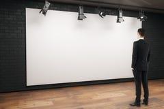 Uomo che esamina tabellone per le affissioni vuoto Immagine Stock