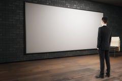 Uomo che esamina tabellone per le affissioni vuoto Immagini Stock Libere da Diritti