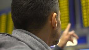 Uomo che esamina tavola elettronica in aeroporto, cercante informazioni di tempo di registrazione archivi video