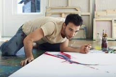 Uomo che esamina tela sul pavimento dello studio Fotografia Stock