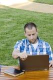 Uomo che esamina un computer portatile all'aperto Immagine Stock