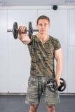 Uomo che esegue allenamento della spalla alla palestra Fotografia Stock