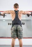 Uomo che esegue allenamento della spalla alla palestra Fotografie Stock