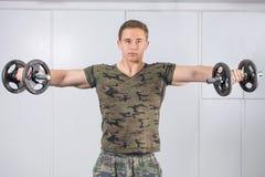 Uomo che esegue allenamento della spalla alla palestra Immagine Stock
