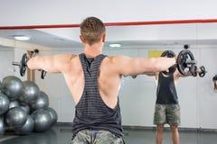 Uomo che esegue allenamento della spalla alla palestra Fotografia Stock Libera da Diritti