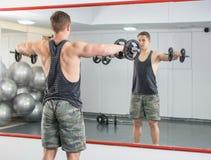 Uomo che esegue allenamento della spalla alla palestra Immagini Stock Libere da Diritti