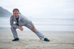 Uomo che esegue allungando esercizio sulla spiaggia Fotografia Stock