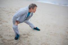 Uomo che esegue allungando esercizio sulla spiaggia Immagini Stock Libere da Diritti