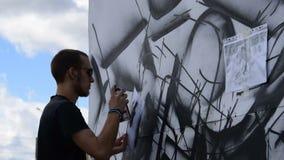 Uomo che esegue le abilità dei graffiti nella via video d archivio
