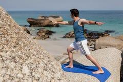 Uomo che esegue yoga su roccia Fotografia Stock Libera da Diritti