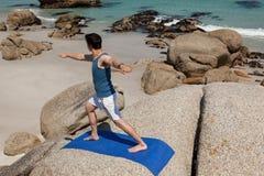 Uomo che esegue yoga su roccia Fotografia Stock