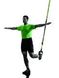 Uomo che esercita la siluetta del trx di addestramento della sospensione Fotografie Stock