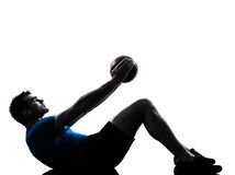 Uomo che esercita posizione della palla di forma fisica della tenuta di allenamento Immagini Stock